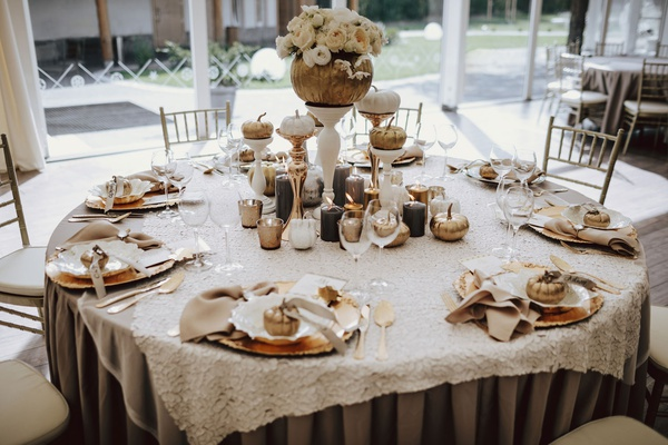 wedding reception table round pumpkin centerpiece with flowers pumpkin place settings escort cards