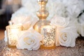 White rose on top of gold sequin tablecloth at wedding table