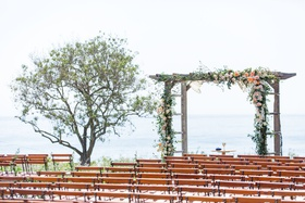 wedding ceremony wood chairs wood arbor greenery rustic chic ocean view ceremony
