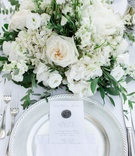 silver charger plate, silver wax seal on menu, white napkin and menu, ivory roses