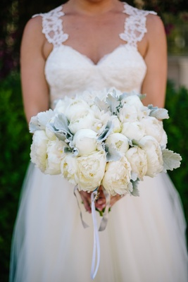 bride in winnie couture holding bouquet of cream peonies and dusty miller