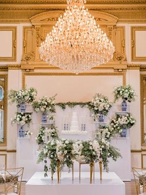 ballroom wedding reception sweetheart table greenery cake wall blue white vase and candlesticks