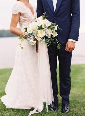 Bride in Carolina Herrera wedding dress groom navy blue tuxedo bouquet with garden rose ribbon