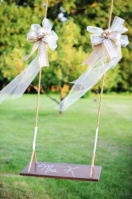 Wedding reception in Pennsylvania country field with a wood and rope swing with gold, white ribbon