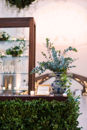 wedding reception bar wood with greenery blue white vase eucalyptus bar menu and shelving