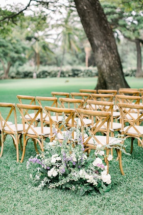 hawaii wedding ceremony outdoor lawn plantation wood chairs greenery purple white flowers entrance