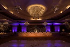 Ballroom wedding with purple lighting, cake, and custom dance floor