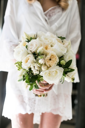 bride in white robe holding ivory bridal bouquet garden rose rose berries greenery elegant classic