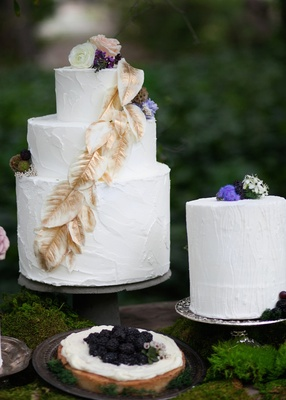 White wedding cake with golden leaves, and white wedding cake with wood grain etchings, flowers