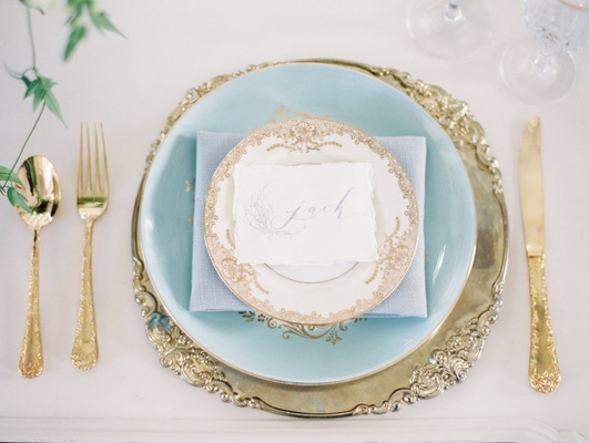 Wedding reception place setting with a gold charger with ornate rim, light blue dinner plate
