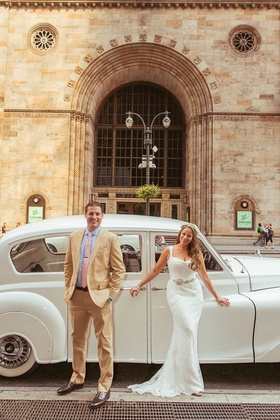 Bride and groom standing in front of white Rolls-Royce car