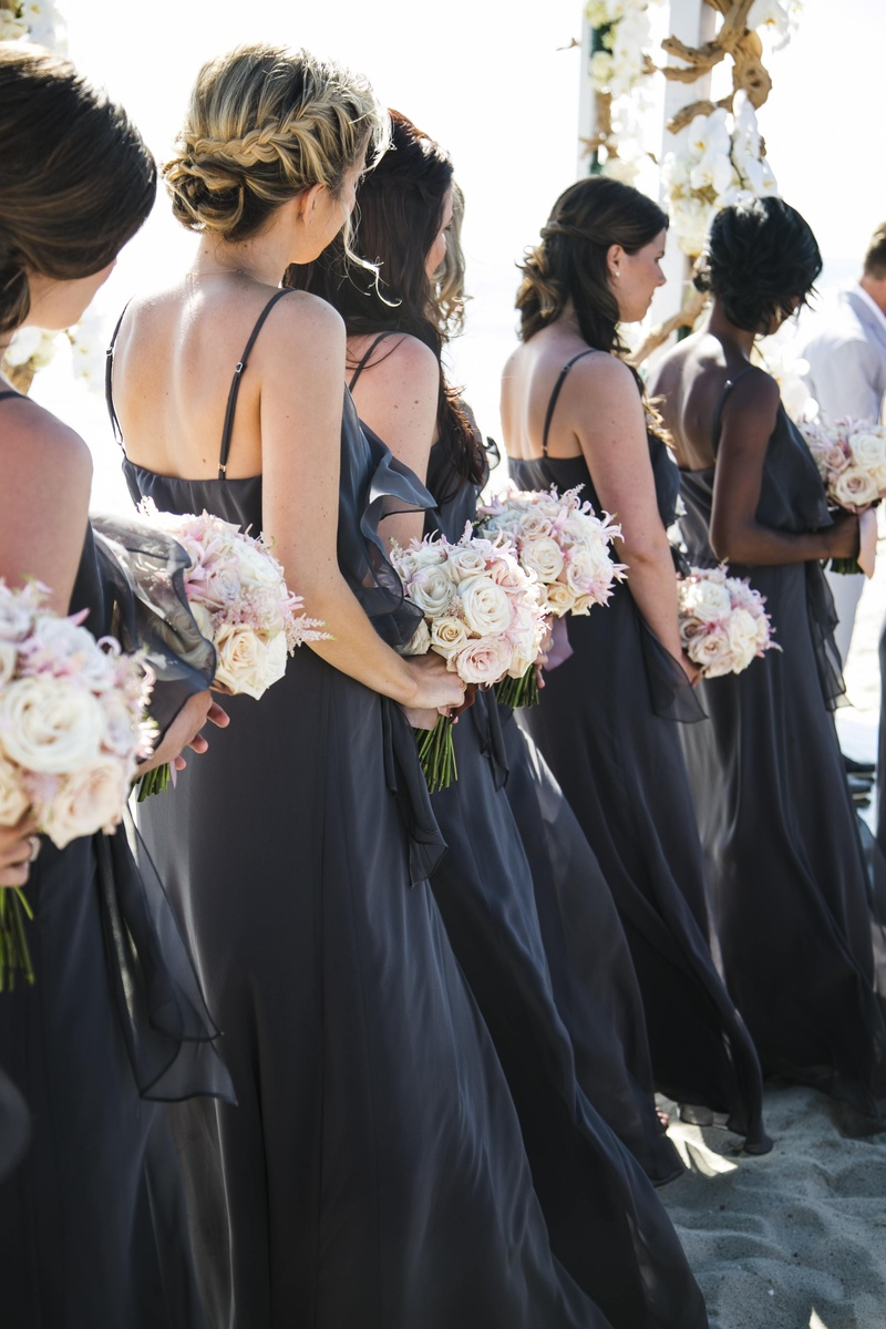 Bridesmaids in floor-length gowns at beach ceremony