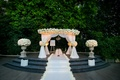 Outdoor ceremony with stone platform and white chuppah with flowers