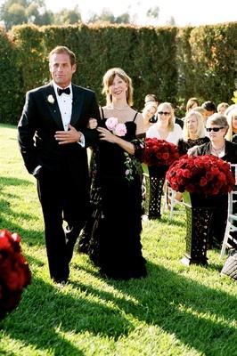 Groom walking mother down aisle in black dress