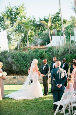 a bride and groom say their vows in front of family and friends on green lawn near palm trees