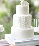 three-tiered round white wedding cake, middle tier with fondant leaf pattern, sugar peony on top
