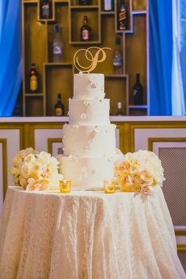 """four tier white wedding cake with floral appliques and a gold """"P"""" cake topper"""