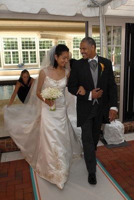 Bride in a Reem Acra gown walking with her father in