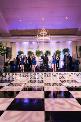White and black checkerboard dance floor in front of live band stage blue sequin dresses black suits