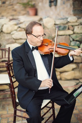 Wedding ceremony string quartet male violin player in tuxedo and bow tie at outdoor wedding venue