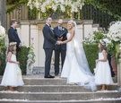 bride and groom officiant best man flower girls outdoor courtyard greenery white flowers ceremony