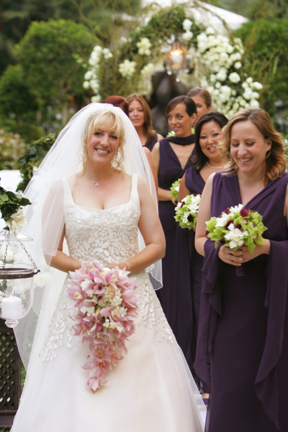 Bride in an A-line gown with a pink orchid bouquet and bridesmaids in purple dresses