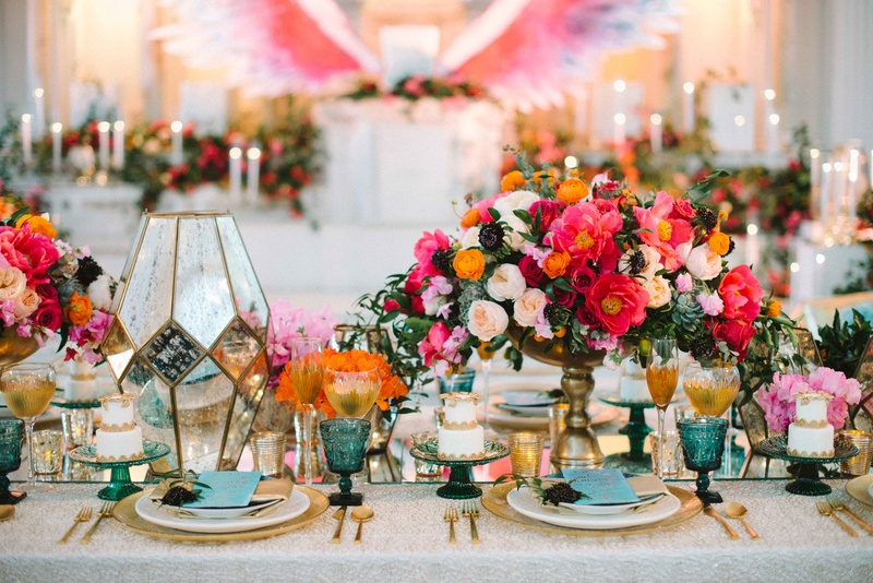bold floral arrangements white linen gold chargers plateware rainbow colors wedding reception