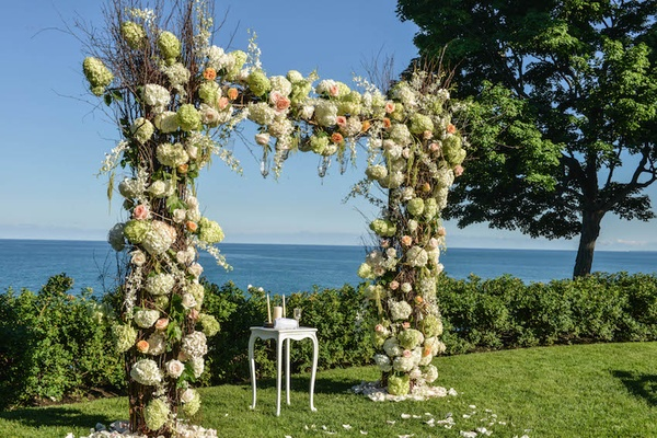 Ceremony arch with white, pink, and green flowers in front of lake