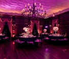 Mansion ballroom wedding reception with lavender lighting