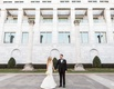 Bride in Ines Di Santo wedding dress holding bouquet and hand of groom with tuxedo bow tie