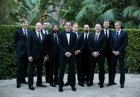 Groom wearing tuxedo and bow tie and groomsmen wearing black suits and ties