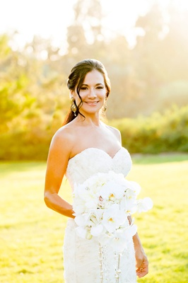 bride in strapless Romona Keveza wedding dress with white bouquet and soft curl in front of face