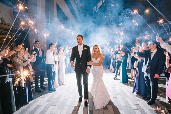 Bride and groom hold each other as they walk through pathway created by guests sparklers night