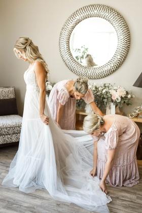 bridesmaids in vintage puff sleeve bridesmaid dresses helping bride into boho wedding dress