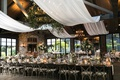 wedding reception white drapery through rafters beams iron chandelier with greenery long table