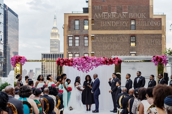 Bride and groom under archway female officiant book bindery empire state building rooftop