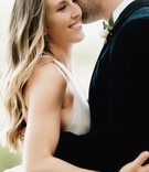 bride in v neck wedding dress with long hair soft curls groom in suit boutonniere