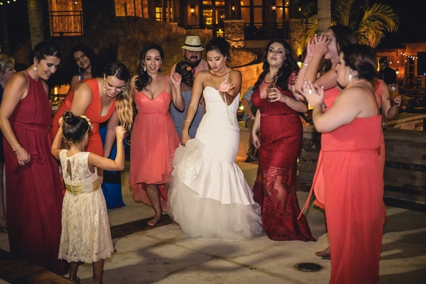 a bride her bridesmaids in coral and red dresses and the flower girl in white lace dance reception