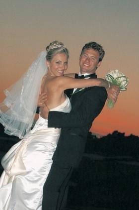 Groom picks up bride in front of Newport Beach sunset