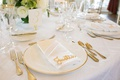 Wedding reception round white table gold charger and flatware name on top of napkin gold decoration