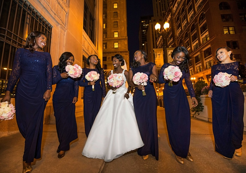 Bride in wedding dress with bridesmaids in long navy blue dresses with long sleeves or cap sleeves