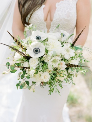 bouquet with anemone flowers, feathers, white flowers, and greenery