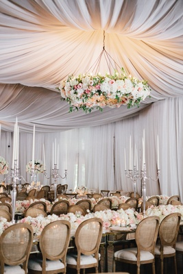 Drapery at wedding reception with large floral chandelier over guest tables long mirror tables