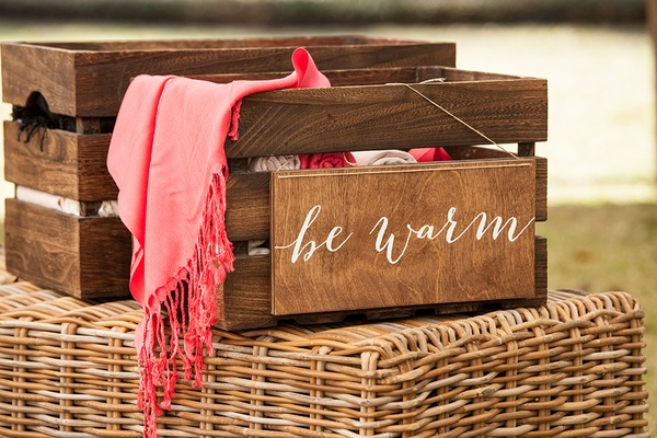 Wooden crate filled with blankets pashminas wedding favor outdoor be warm wood calligraphy signage