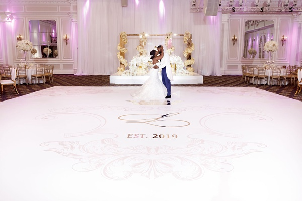 wedding reception white dance floor pink monogram and gold details in front of sweetheart table