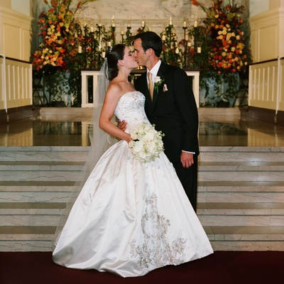 Bride in Reem Acra ball gown and groom kiss