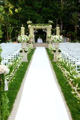 Outdoor ceremony on grass with white aisle runner and flowers