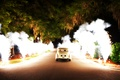 Pyrotechnics line a driveway as newlyweds drive off