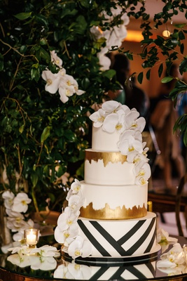 wedding cake four layer black white stripe geometric design gold foil and white orchid decorations