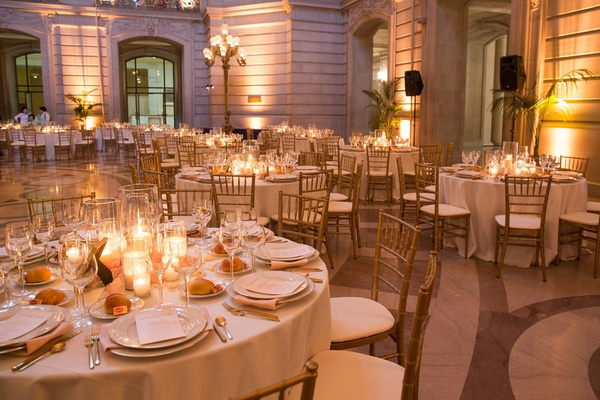 Wedding reception tables with candles in hurricanes, pink petals, gold chiavari chairs